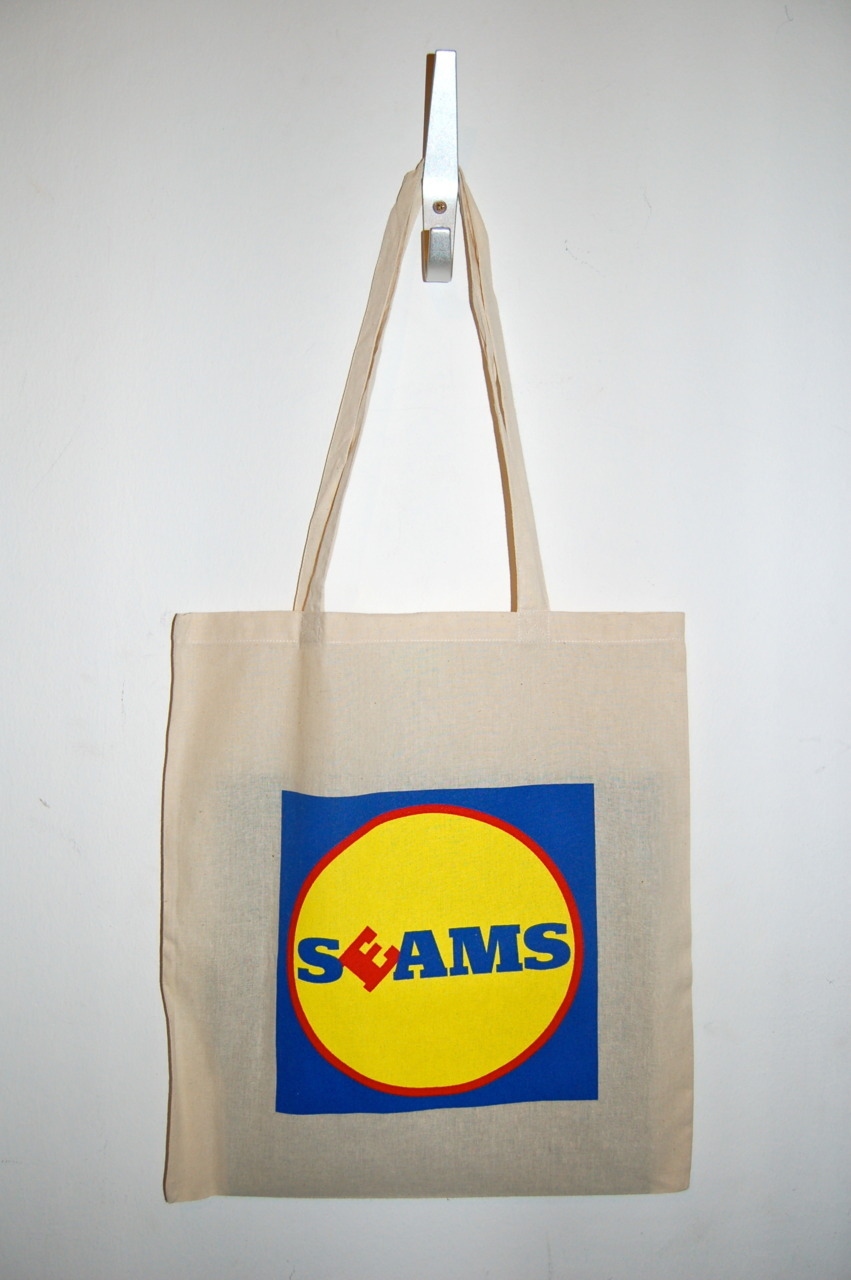 "Always need more tasty totes. seams:  *** SPONSORED MESSAGE FROM SEAMS*** Confuse your local supermarket shoppers, and help care for the environment with this Seams tote bag. Screen printed and good for you. Big enough to carry 12"" records, if you like that sort of thing. Edition of 100. Available as a bundle with any music downloads at seams.bandcamp.com"