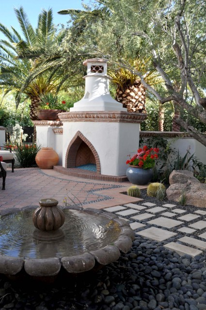 A Mediterranean style terrace is embellished with a water fountain and brick and stucco outdoor fireplace (via Carson Poetzl, Inc.)