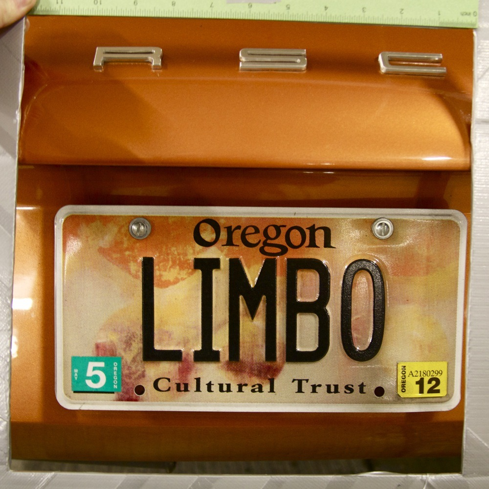 "Oregon state vanity license plate, ""LIMBO"", on orange Porsche 911, parking garage, Pearl District."