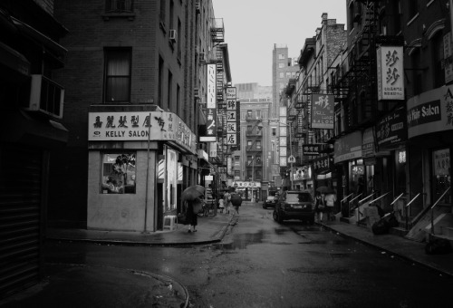 "Pell Street, Chinatown in the rain. New York City.  Under the weight of the sky's tears streets glisten reflecting the gleam in the eye of the clouds overhead. The day washes away slowly: its sorrows and joys melt into puddles under-foot.   It's on these sorts of evenings that all of the cares in the world pale in comparison to the momentary haze that engulfs the city: a sultry, sorrowful, sedate embrace.   —-  View this photo larger and on black on my Google Plus page  —-  Buy ""The Gleam in the Eye of the Clouds - Chinatown - New York City"" Posters and Prints here, View my store, email me, or ask for help."