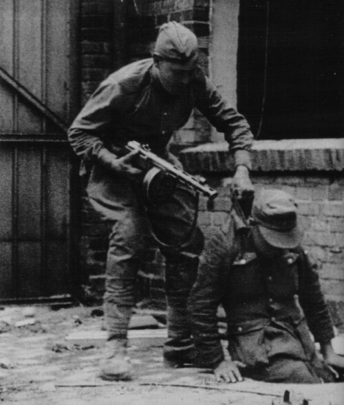ausschreitungen:  A German soldier being taken prisoner by a Red Army fighter on a street in Berlin.