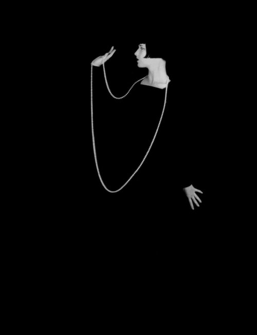thegirlisbad:  1928 — Legendary American film actress, Louise Brooks (1906 – 1985), wearing a long pearl necklace  against a black background. — Photo by Eugene Robert Richee © Sunset Boulevard