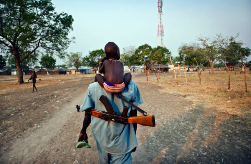"gunsandposes:  In South Sudan, a Descent into Violence: ""A man carried his daughter as people who fled the small town of Pibor returned after fleeing the violence there.""[New York Times]"