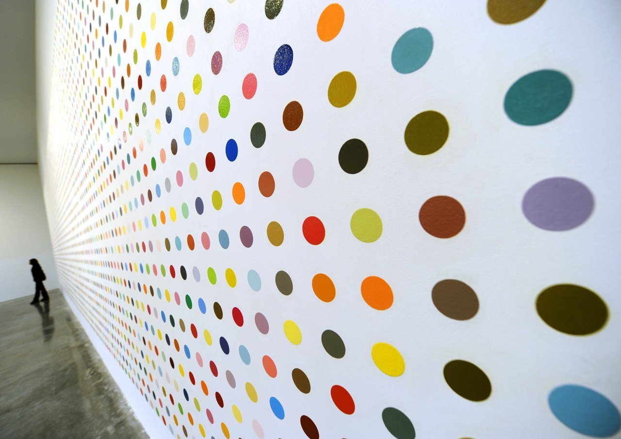 "Daily Pic: A full wall of dots by Damien Hirst, from the spot-painting extravaganza that is now filling all the world's Gagosian galleries. (And that the Daily Pic can't seem to shake free of.) Of the project's 331 spotted canvases, the only ones that fail, as art, are the ones that could count as ""successful"" abstract paintings. The whole glory of Hirst's project, it seems to me, is that it blows-off stale, Old Masterish notions of fine-art connoisseurship. Hirst drowns the connoisseurial eye in a sea of spots whose colors have been chosen arbitrarily, and so can't be any more significant, artistically speaking, than the random colors floating on an oil slick. When Hirst's spot paintings look good, it's an accident that needs to be ignored. By refusing to let us fall back on easy aesthetic judgments, picture by picture, Hirst forces us to work at what his flood of picture-making might mean, as a whole. Hirst's dots don't provide the quick read, as eye candy, that gets some critics to dismiss them. I'd say the project demands the kind of  slow, attentive thought you give to the complexities of a great Cezanne or Picasso. (Photo by Timothy A. Clary, AFP / Getty Images)"
