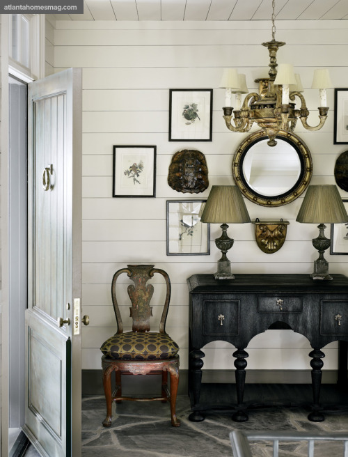 In the entry hall, a sophisticated collection of art and antiques is balanced by North Carolina fieldstone floors and horizontal board walls that convey a farmhouse feel. (via Country Chic | Atlanta Homes & Lifestyles)
