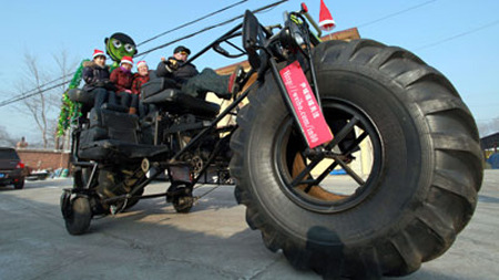 "rocketboom:  Big-Wheel - This 10-foot high, 18-foot long bike weighs about a ton, and cost Yali Zhang, the Chinese mechanic who built it, almost $4,000 to complete. He evidently built it as a gift to ""inspire"" his son, an animation artist who lives a long way away from his family. Evidently Zhang not only quit his job to take on the project, but spent the family savings on what essentially began as a pile of trash... The things people do for their kids, huh?"