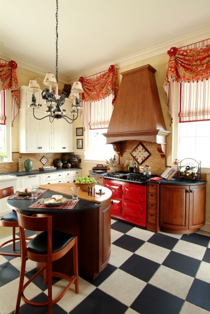 Retro blends with French Country in this bright and charming kitchen, with its custom window treatments, red Aga cooker, and dramatic black and white checkerboard floor. (via K.Marshall Design Inc.)