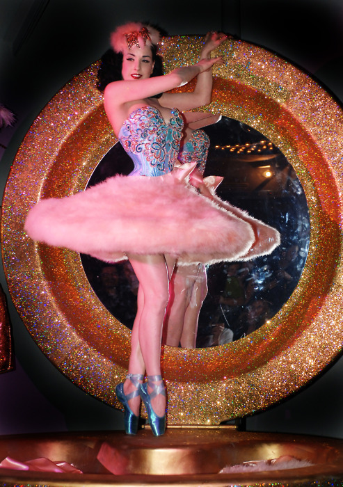 Dita von Tease, in an embroidered corset and a pink fur tutu, with blue  ballet pointe shoes in front of a glittery Stargate.  Too much?