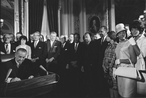 "pantslessprogressive:  ""Prior to the passage of the Voting Rights Act of 1965, African-Americans and many others faced regular and malicious restrictions to the free exercise of their constitutionally protected right to vote, especially in my native South. Literacy tests, poll taxes, and grandfather clauses: many insidious techniques were used by certain states to restrict, confuse, and write off, marginalize and disenfranchise so many eligible citizens from voting simply because of the color of their skin. Southern governors and those in Washington comfortable with the status quo hid behind arguments about ""states rights."" Yet these laws were little more than legislated racism and all knew the real goal behind their unequal effects. In a 1957 speech titled 'Give Us The Ballot,' Dr. King spoke plainly about the imperative of equal voting rights. 'So long as I do not firmly and irrevocably possess the right to vote I do not possess myself. I cannot make up my mind — it is made up for me. I cannot live as a democratic citizen, observing the laws I have helped to enact — I can only submit to the edict of others.' For Dr. King, the right to vote was sacrosanct and foundational. It is the very essence of our social contract. Free elections create legitimacy. They imply the consent of the governed. He knew that unfair elections laws did not just hurt minorities or the working poor, they rendered hollow the very essence of American government. It's a message that's as true today as it was then. The 47-year old Voting Rights Act has stood the test of time, but there are new obstacles to the ballot springing up in today's America. Around the country, conservatives in state legislatures are attempting to put fresh roadblocks in the path of this most basic right. The latest vogue in anti-suffrage legislation is mandatory photo ID laws. […] These laws disproportionately impact minority communities — groups much more likely than white voters to lack photo identification for reasons as simple as the fact that they may not own a car and use the city bus to get to work. According a study published in 2006 by the Brennan Center for Justice at the New York University School of Law, as many as 23 million American citizens — that's 11% of those of voting age — lack the government-issued photo ID many of these laws demand."" - Donna Brazile [Photo: Martin Luther King Jr. and other civil rights leaders watch President Lyndon B. Johnson sign the Voting Rights Act on August 6, 1965. Credit: National Archives]"