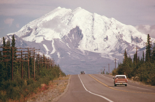 Looking east along Alaska's Glen Highway, toward Mount Drum (Elevation 12,002 Feet) at the intersection of the highway and the under-construction Trans-Alaska Pipeline in August 1974. The 48-inch diameter pipeline will cross the roadway between the two vehicles. The exact point is marked by a pair of wooden stakes along the right shoulder at Mile 673. (Dennis Cowals/NARA)