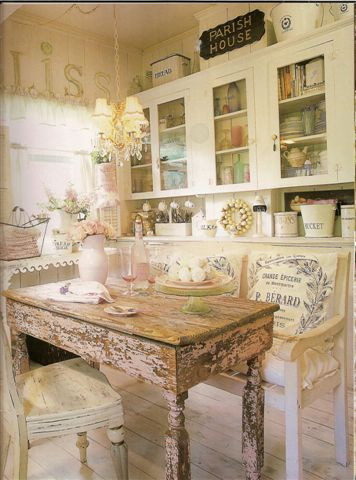 shabby chic kitchen: i love the pastel little things in the cabinet. also, the table.