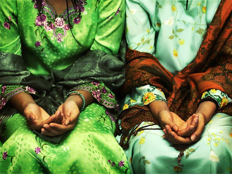 Folded Hands, BruneiPhoto: Adam Hanif Colorful shawls and flowered dresses accentuate these Bruneian girls as they practice for a traditional Malay family gathering. There hands, folded together, symbolize humility and peace.
