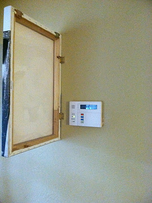 diy photo canvas alarm panel cover :the third boob  Using a stretched canvas is a great way to cover a thermostat in the middle of the wall as well. Or old phone jacks or ill placed (smaller) fuse panels. Alternatively you could hang the canvas over the panel but the hinges make it less cumbersome.
