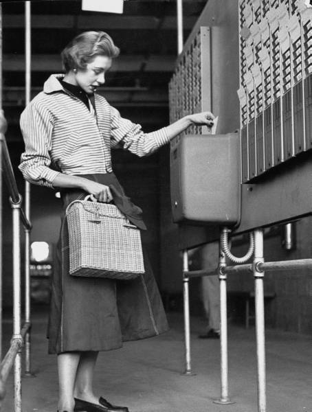 A young working woman getting her time card punched. Photograph by Yale Joel. Long Island, New York, USA, March 1953.