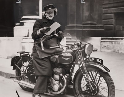 A lady motorcycle messenger bringing a letter to a Government office in London. April, 1940. From the Yorkshire film archives.