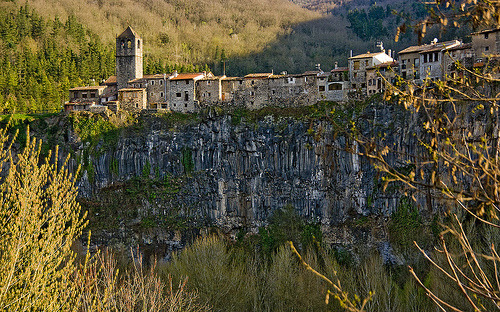 scinerds:   A town above the lava flow (by SBA73)  Castellfollit de la Roca is a town of approximately 1,000 inhabitants in an area of less than a square kilometre, making it one of the smallest towns in Catalonia. This small urban area is bordered by the confluence of the Fluvià and Toronell rivers, between which the town's spectacular basalt cliff rises.The basalt crag where the town is situated is over 50 m high, almost a kilometre long, and is the direct result of the erosive action of the rivers Fluvià and Toronell on the remains of the lava flows from the volcanic eruptions which took place thousands of years ago.The lava, once solidified, became basalt; a hard rock which takes on different forms, depending on the cooling, contraction, and splitting processes of the lava. The cliff is the result of two lava flows; the first took place 217,000 years ago, and originated in the area of the village of Batet, and has formed slabs, the second, a more recent formation from the volcanoes of Begudà is 192,000 years old, and has formed into prismatic shapes.