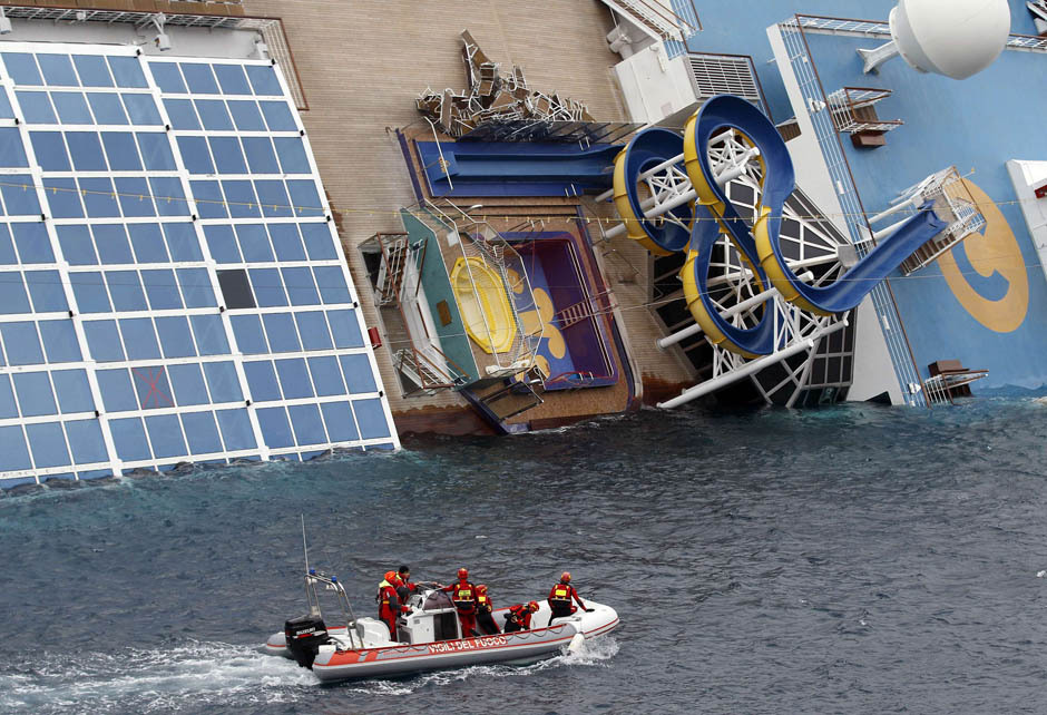 Rescue workers from the Italian Coast Guard inspect an upper deck of the partially-submerged Costa Concordia.  Officials say five more bodies have been discovered inside the ship, bringing the total of confirmed dead to 11.  (Photo: Max Rossi / Reuters via the National Post)
