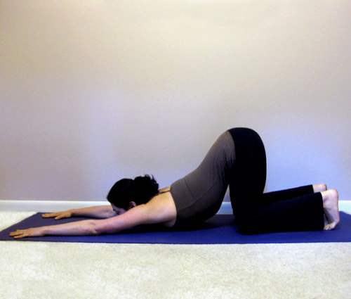 kicksomeasana:  Uttana Shishosana (Extended Puppy Pose) A cross between Child's Pose and Downward Facing Dog.    Come onto all fours. See that your shoulders are above your wrists and your hips are above your knees. Walk your hands forward a few inches and curl your toes under. As you exhale, move your buttocks halfway back toward your heels. Keep your arms active; don't let your elbows touch the ground. Drop your forehead to the floor or to a blanket and let your neck relax. Keep a slight curve in your lower back. To feel a nice long stretch in your spine, press the hands down and stretch through the arms while pulling your hips back toward your heels. Breathe into your back, feeling the spine lengthen in both directions. Hold for 30 seconds to a minute, then release your buttocks down onto your heels.