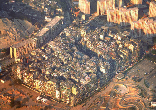 killytron:  The Kowloon Walled City, a maze of apartments, walkways and stairs, so cramped that sunlight couldn't reach the lower levels and had a population density of 1,255,000 per square kilometre.