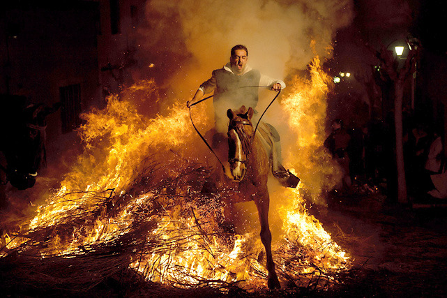 "A man rides a horse through a bonfire in San Bartolome de Pinares, Spain on Monday in honor of Saint Anthony, the patron saint of animals. On the eve of Saint Anthony's Day, hundreds ride their horses trough the narrow cobblestone streets of the small village of San Bartolome during the ""Luminarias,"" a tradition that dates back 500 years and is meant to purify the animals with the smoke of the bonfires and protect them for the year to come. (AP Photo/Daniel Ochoa de Olza)"