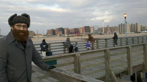 "Coney Island, off-season. I had a free afternoon in the middle of the week, so it was sort of a spontaneous decision to travel south with a Brooklyn friend and see Coney Island and the ocean. I'd never been south of Prospect Park before. Brooklyn is huge and I've never seen most of it. Riding down, I'm surprised to see the residential areas clustered around the southernmost part of Brooklyn look more like South Minneapolis than like other parts of Brooklyn.  Everything on the boardwalk is closed, and the beaches are empty. The relatively temperate weather in the middle of January makes the whole scene even more surreal. On the beach, we meet a lone reporter from the New York Post, who asks us our opinion one building casinos on Coney Island. I tell him I'm just visiting, and he loses interest in speaking to me. He interviews my friend, and seems to be trying to coach her into saying something pro-casino. He's every bit as obnoxious as you'd imagine a New York Post reporter to be. I realize I should have given him a fake name like ""Randy Slurdevant"" and told him I lived in some obscure neighborhood like Ozone Park and said, ""I think they should tear the whole boardwalk down and build nineteen huge casinos, each one bigger than the last! Maybe they can get Donald Trump to do it! That guy is a winner!"" The only people out at all, besides New York Post reporters, are people on the pier fishing. There's a few dozen of them bundled up in winter clothing and sitting on plastic buckets and bobbing fishing poles over the edges. It's fascinating. The pier is littered with shimmering, iridescent fish scales and drops of bright red fish blood. I walk past one guy fishing, and go into my usual Studs Terkel routine: ""What sort of fish do you usually catch here?"" I don't know anything about saltwater fishing. I'd like to learn. The guy frowns and silently makes a circular motion with this hand. The meaning is unclear to me. It seems to mean one of three things: 1.) ""Oh, you know, we catch all kinds."" 2.) ""Sorry, I don't speak English."" 3.) ""Please fuck off."" The third seems the most likely. Walking away, I express surprise to my friend. She is a native Manhattanite, born and raised near Union Square. ""This isn't the Midwest,"" she says. ""You can't just walk up to anyone and expect have a conversation."" I am even more surprised by this. ""Exactly!"" I say. ""This isn't the Midwest! People don't mind talking to strangers here!"" I realize my friend and I have wildly divergent views on the social habits of New Yorkers vs. Midwesterners. I always thought New Yorkers were pathologically opinionated loudmouths that were willing to get into noisy conversations with anyone. I always thought Midwesterners were stand-offish and tight-lipped and would do anything to avoid talking to a stranger. She always thought New Yorkers were privacy-obsessed jerks that didn't have the slightest bit of interest in making any sort of engagement with the teeming masses of humanity surrounding them. She always thought Midwesterners were warm, genuinely friendly people happy to make small talk with anyone. I'm still not sure, though if the circular hand motion was a ""fuck off"" sign, my friend may have a point. This winter, I'll have to go find some people ice-fishing out on one of the city lakes around Minneapolis and ask them about what they're doing. Then we'll know for sure."