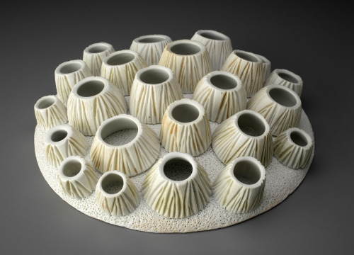"Suzanne Stumpf: Urchin, 2010, 3""h x 11"" w x 11"" d, handbuilt porcelain with wheelthrown components; oxidation fired to cone 10Urchin is an interactive sculpture as well as a puzzle. There are 13 barnacle-like components that have been attached (through firing) to the perimeter of Urchin, and there are 10 others that are removable. The movable ""barnacles"" can be used to make multiple arrangements (on and off Urchin). However, Urchin is also a puzzle: there is only one way that the free ""barnacles"" can all be fit securely and comfortably into the center space."