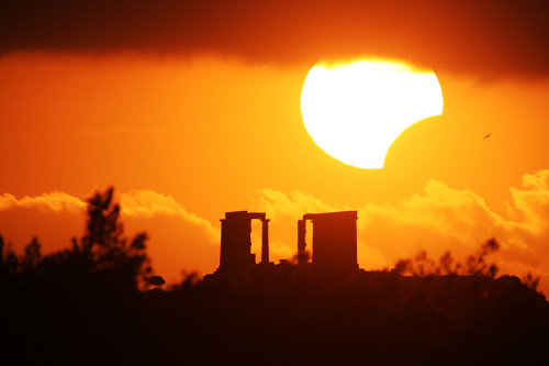 Eclipse over the Temple of Poseidon  Credit & Copyright: Chris Kotsiopoulos & Anthony Ayiomamitis  The Moon moved to partly block the Sun for a few minutes as a partial solar eclipse became momentarily visible across part of planet Earth.  In the above single exposure image, meticulous planning enabled careful photographers to capture the partially eclipsed Sun well posed just above the ancient ruins of the Temple of Poseidon in Sounio, Greece.  Unexpectedly, clouds covered the top of the Sun, while a flying bird was caught in flight just to the right of the eclipse.