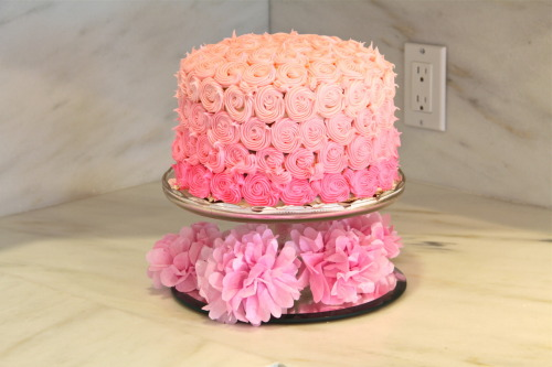 "Ombre Pink Swirl Cake We just celebrated the upcoming arrival of my niece at my sister's Sprinkle this last weekend.  In our preparation, I came across this lovely cake on Pinterest and then became obsessed with Glorious Treats, the blog it originated from! Please follow along her blog for the recipe details.  Ill walk you through briefly what we did.  We started with 2, 9"" round tins and floured them and placed a piece of parchment paper in each.  We re-used those two rounds for each cake.  Unless of course you have 5 round cake tins.   Mix your batter.  If you have a mixer, use it!  This cake takes awhile and this really helps a lot!  Once you have your batter, separate into 5 bowls evenly.   Then start the coloring process.  Start with the darkest color first!  We got gel food-coloring (from Michael's) in Pink, Rose, and Violet.   Use the Violet in the darkest color only.   Add the batter to the prepared cake pans, bake and let fully cool.     Follow Glorious Treat's recipe for Buttercream Frosting, but double it if you are using a 9"" cake.   Again, use your mixer if you have one. Divide the frosting into 4 bowls.  One bowl with a but more than the others.  That will be your lightest color that will be used for the top and side row of Swirls.   Color the frosting as you did with the batter (but this time you dont need the violet color for the darkest color).  Reserve a extra amount of white frosting (1 cup at minimum- more if you use a 9"" cake) in the mixing bowl to use between the layers and to use as the think crumb coat.   Time to assemble the cake! Prep your cooled cakes by using a sharp knife to make sure they are all flat and easily stackable.  Because you already have a 5 layered cake and a ton of frosting, Glorious Treats suggests adding a warmed Cherry Jam between the layers.  Get any Cherry Jam from the store and pop it in the microwave to warm it.  Place your darkest layer down on your cake plate. (NOTE!  you are not picking this cake up again, so if you want to put a doily down, do it now!). Paint on some warmed Jam.  Layer with a thin layer of frosting and add the 2nd darkest cake on-top and  repeat with all layers.  Crumb-coat the cake with a thin layer of frosting so it is all even for the swirls.  Place in the freezer for 15 mins.   With a Piping bag and a #21 tip (or close to it) star, fill the bag with the darkest color.  Remove the cake from the freezer.  Start at the bottom and make 1 1/2 ""rose"" swirls or ""c""s with a long tail and I see them. Continue around the bottom of the cake.  Once you finish the row in one color, move onto the other colors.  Some spots you may not completely fill.  Just go back and fill in with ""mini swirls"" or dots of frosting until the cake is covered."