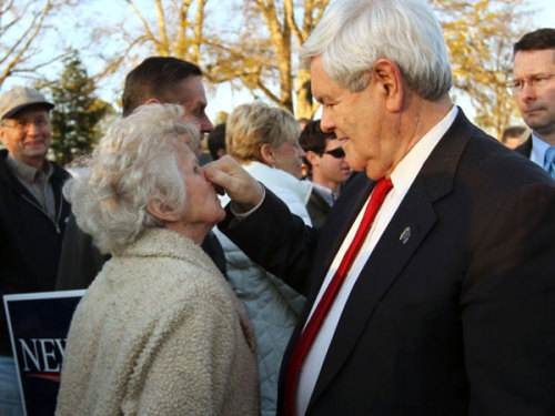 "thefrisky:  Newt Gingrich Plays ""Gotcha!"" With An Old Lady - The Frisky  Newt Gingrich holding an older woman's nose."