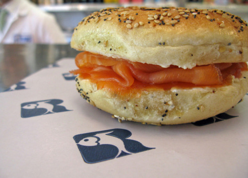 The Russ & Daughters Classic bagel and lox: hand-sliced Gaspe Nova smoked salmon, with all-natural cream cheese, on a traditional hand-rolled water-boiled bagel. (It's okay to eat it in the shop, while you wait for the rest of your order at the counter, just like this customer is doing right now!)