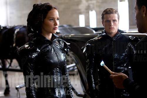 Check out a NEW photo from THE HUNGER GAMES featuring Katniss  & Peeta in their chariot outfits, with Cinna ready to light them on  fire — plus a slideshow of all movie images to date!