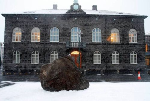 "Enormous rock in front of the Icelandic parliament When parliament building employees arrived at work this morning they discovered a giant rock sitting in front of the building. Later this morning it became clear that the rock was part of Spanish artists Santiago Sierra's NO global tour. Previously he attracted attention when he drove a truck around the streets of Reykjavík with a giant NO on the truck bed. This giant rock or ""The Black Cone, Monument to Civil Disobedience"" is according to the Reykjavík Art Museum a ""reminder of the importance of civil liberties, including the right to refuse to obey laws and commands of the government."" Apparantly it is inspired by the series of protests that have taken place in front of the Icelandic parliament building since the bank crash three years ago. Those same protests were an inspiration for protests in Spain, perhaps prompting Sierra to come to Iceland. Today at one o'clock (Icelandic time) Sierra will drive a half meter long steel cone into the rock and break it and thus breaking the establishment I suppose."