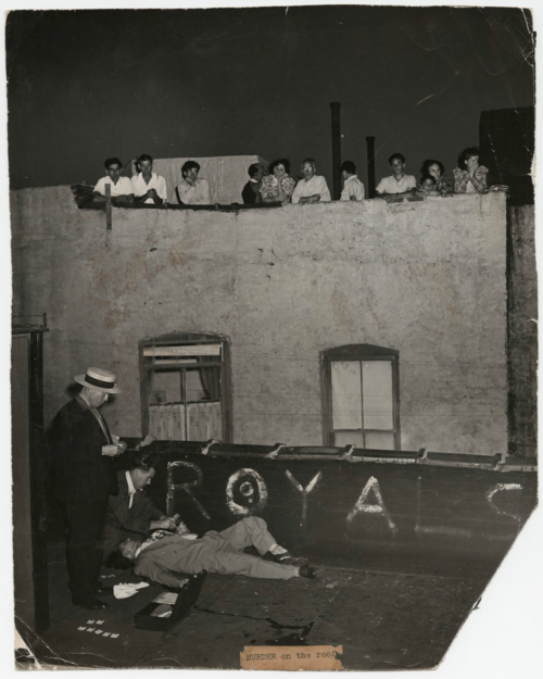 Murder on the roof. Auguest 13th, 1941. ~~> via NYT Lens - Weegee's Killer Decade  On the lineup platform at the police headquarters. Circa 1936. Steps away from the sanitized, commercialized and pacified Times Square is a portal to a sinister urban past, where two-bit hoods lay sprawled in pools of blood with stogies clenched in their lifeless jaws, watched over by the police and the curious alike. It's a world of men with guns and hats who played their final hands under elevated tracks and tenements that have long since vanished.