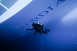 inothernews:  EPITAPH   An Italian police diver inspects the hull of the partially submerged Costa Concordia on Thursday.  Officials are continuing the search for 21 missing passengers and crew; the death toll stands at 11 as reports reveal the captain, Francesco Schettino, waited 73 minutes to sound the evacuation alarm after the ship struck underwater rocks.  (Photo: EPA via the Wall Street Journal)