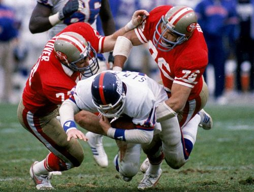 siphotos:  Giants quarterback Phil Simms gets tackled by 49ers defensive ends Jeff Stover (No. 72) and Dwaine Board during the 1984 NFC Divisional Playoff game at Candlestick Park. The 49ers won 21-10. The two teams will face off on Sunday for a Super Bowl berth. (George Rose/Getty Images) GALLERY: Giants-49ers Playoff History | Matchups To WatchVIDEO: Giants defense talks about stopping Alex SmithBANKS: Giants and 49ers set to renew epic playoff rivalry