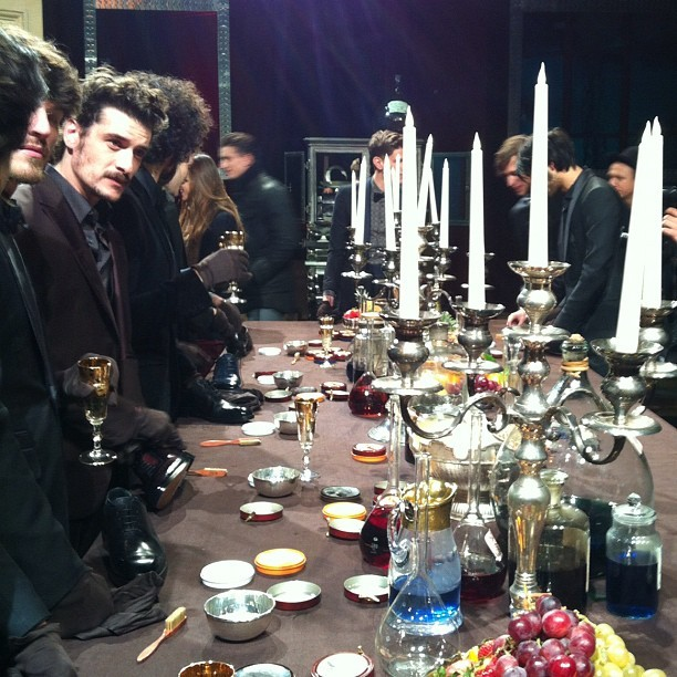 Berluti models polishing shoes at the dining table
