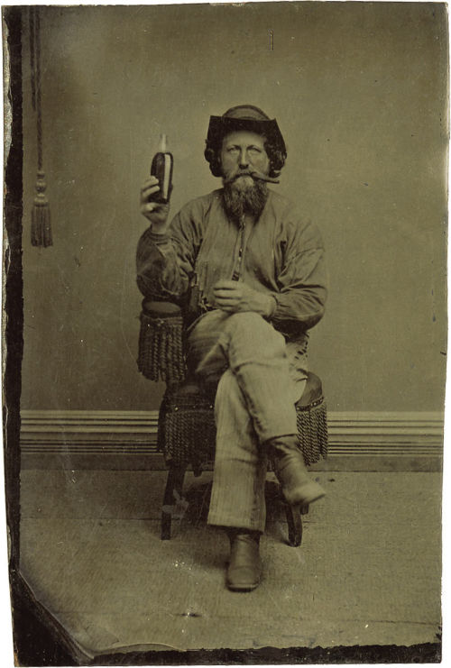 ca. 1870's, [tintype portrait of a bearded gentleman smoking a cigar and holding up a bottle of whiskey] via Heritage Auctions
