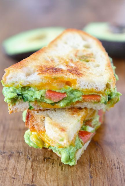 GUACAMOLE GRILLED CHEESE SANDWICH Ingredients: To make the guacamole… 2 ripe avocados 1/2 small onion, minced 1 clove garlic, minced 1 small jalapeño, stems and seeds removed, minced 2 tablespoons cilantro leaves, finely chopped 1 tablespoon of fresh lime juice 1/2 teaspoon coarse salt A dash of freshly grated black pepper 1 Roma tomato, chopped Rest of Sandwich…  4 slices crusty white bread 4 slices Cheddar cheese Butter, for buttering bread Directions: To make the guacamole-cut avocados in half. Remove seed. Scoop out avacado from the peel, put in a large bowl. Using a fork, mash the avocado. Add the onion, garlic, jalapeño, cilantro, lime juice, salt and pepper. Stir until well combined. Add the chopped tomato and stir. Heat a pan or griddle to medium-high heat. Spread desired amount of guacamole on both slices of bread then top with cheese. Butter outer slices of bread and grill on one side for about 2 minutes or until golden and crispy. Flip the sandwich and grill until golden brown. Make the other sandwich the same way and serve warm.