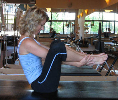Daily Pilates Pose 33: The Seal 1. Sit at the front of your mat with your knees bent to your chest and heels together. Open your knees to shoulder width and slide a hand under and around each ankle. Pull your feet up off the mat until you are balancing on your tailbone. 2. Roll back, pulling your feet with you. Do not roll too far onto the back of your neck. Balance on the back of your shoulders instead, allowing your legs to extend slightly until your feet are over your head. 3. Balancing in the backward position, clap your heels together three times. 4. Exhale as you roll forward, tucking your chin into your chest. Pull your ankles to come up. 5. Balance in the forward position and clap your heels together three times. 6. Repeat the sequence 6 times. Use the control  of your core and breath to bring you forward and back.