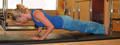 Daily Pilates Pose 34: Push-Ups 1. Stand at the back of your mat with your feet together and slightly turned out. 2. Exhale and walk your hands down the front of your legs until your palms are pressing into the mat. 3. Inhale and walk your hands out on the mat until your hands are directly under your shoulders. 4. Exhale and lower your hips until they are in line with the rest of your body. 5. Perform three push-ups by bending and straightening your arms with your elbows held tightly to your sides. 6. On your last push-up, fold in your center, bringing your chest toward your legs. Exhale as you press your palms and heels firmly into the mat and pull your navel up to your spine for a complete stretch. 7. Inhale as you walk your hands back toward your feet. 8. Exhale and roll back up to a standing position. 9. Repeat the sequence 3 times. Do not allow your middle to drop, as that will place most of your body's weight onto your shoulders.