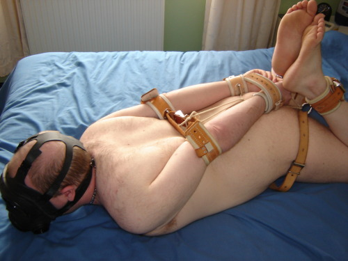 Hogtied in medical restraints and an S10 gasmask