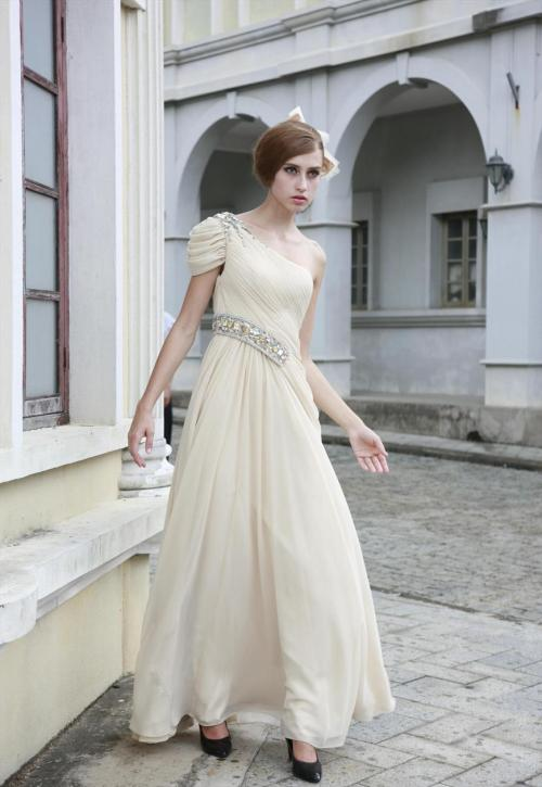 Cream Asymmetrical Jewelled Wedding Dress £285.00  Trendy cream wedding dress featuring asymmetrical A Line silhouette with chiffon full length skirt, diagonally ruched bodice with jewelled side waist belt, and ruched drape short sleeve with jewel embellishments on shoulder. Send us a message to inquire about our plus size or if you like this dress in another colour of your choice.