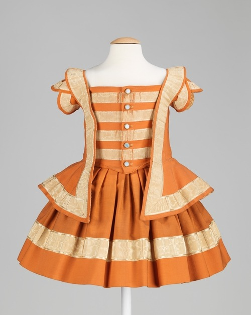 A boy's bright orange wool dress with ribbon trim dating to 1856.