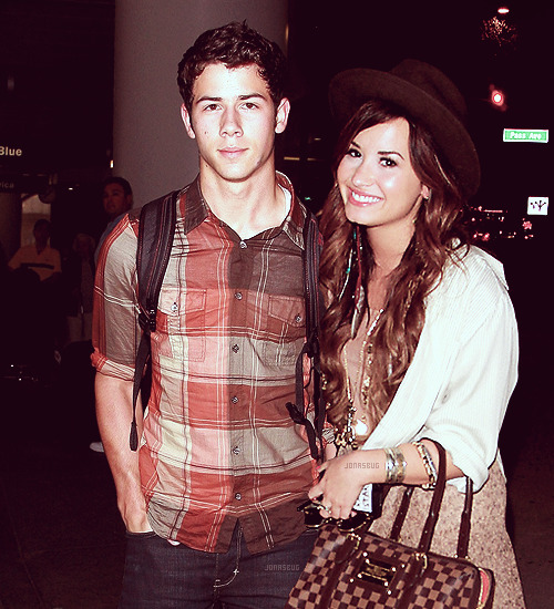 """Dammit."" Nick muttered with a sigh as he handed Demi her luggage. He could see the flashes from the inside of the airport. To him, camera flashes meant only one thing - absolute and certain death. ""What?"" Demi asked as she looked over at him, pulling up the handle on her Louis Vuitton suitcase. The camera's meant nothing to her; she wasn't as private as he was. She always smiled and waved and went about her business as if they weren't there. But not Nick - he couldn't stand having a forty year old man shoving a camera in his face. And it's not like Demi didn't get tired of it, too. She just dealt with it better than he did. ""Uh… Nothing."" Nick shook his head, taking his own backpack and throwing it over his shoulders. ""You ready?"" He held out his hand for her and she nodded, taking it and lacing their fingers easily. He gave her hand a light kiss and smiled, glad to see the brilliance reflected in her face. He almost wished they had stayed in Cabo, just lived there for a while. But they had to get back to reality eventually. And it's not like their realities were bad or anything, it was just nice to get away for that one week. To just lay on the beach and not have to worry about futures or failing careers or anything. They just had each other and it was simple enough to work. And that's just the way he liked it. They walked out of the airport hand in hand, Nick pulling along her suitcase and leading her to where their car would be pulled around by none other than Big Rob. But in the less than two minutes that it took for him to drive around, they were in a chaotic mob of flashes and questions.  He tried not to sigh, but something about the lateness of the hour and the dark of the night meant that to suppress such an emotion would be nothing short of impossible. Demi, hearing this, knew there was nothing she could do expect hold his hand tighter. It was reassuring to know she was right there with him, bearing the same burden (if you could even call it a burden without sounding spoiled) he was but with more grace and elegance that he could even hope to capture in a million lifetimes.  He didn't know how she did it, especially after treatment. All the questions being shouted in your ear, all the lights blinding your eyes. It was annoying to say the least and he sometimes felt like giving them all a good punch in the face. So he didn't get how she could just smile and stand there. But it just worked that way, he supposed. Because he balanced her out in this in the same way he balanced her out in dealing with stress. When she would freak out and claim she just couldn't do it anymore, he would just pull her into his arms and talk quietly until he could get her to laugh and calm down. So they had different strong points in their relationships and he liked it that way. And as far as he could tell, so did she. It's kind of what made them absolutely perfect for each other. ""How was Cabo?!"" ""Where did you go?!"" ""Did you drink?!"" ""Is it true that you're living together?!"" ""Nick, have you picked out a ring?!"" ""Demi! Do you think you'll ever marry him?!"" ""How does it feel dating your brother's ex?!"" ""Is it all for publicity?!"" ""Hi guys."" Demi just smiled, standing up on the curb next to Nick and leaning into him the way she did whenever she was tired. ""Give us a kiss!"" ""What's your favorite thing about each other?!"" ""Did you guys see the trending topic the other day?!"" Nick somehow compressed another sigh, wrapping his arm around her protectively as he watched for the black SUV to be heading around the bend. He saw it after another moment and took a deep breath of relief, half thankful and half angry for the fact that Big Rob wasn't there the second they'd walked out of the airport. He just needed to go home and go to bed at this point. He looked down at Demi, a small curve of a smile emerging on his lips as he saw her politely grinning at the cameras. ""They just want a show."" She had told him when they'd first started dating. ""So I figure why not smile and let them have their pictures? It doesn't do me any harm."" He wished he could think of them in that light, but they were just so goddamn obnoxious.  But he figured if he wasn't going to smile, he might as well just look up and make eye contact. Give them a show, even if it was a small one. After all, it wasn't like it did him any harm."