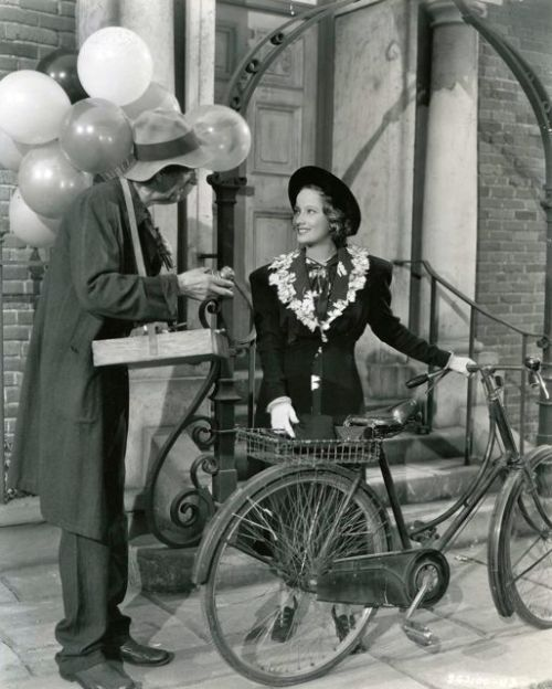 Merle Oberon walks a bike. Balloon man hawks his wares.