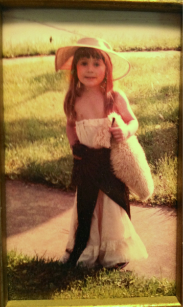 "4 year old me, rocking my favorite dress, hat, and scarf.   I also was obsessed with the piece of wool I am carrying in the photo. It was like a teddy bear to me, and I named him ""Little Wooly"" and took him everywhere with me. I was a weird child, what can I say?"