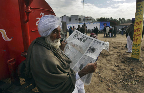 fotojournalismus:  Mukhtsar, India. A man reads a newspaper near the venue of an election rally in Punjab state, Jan. 22, 2012. [Credit : Altaf Qadri/AP]