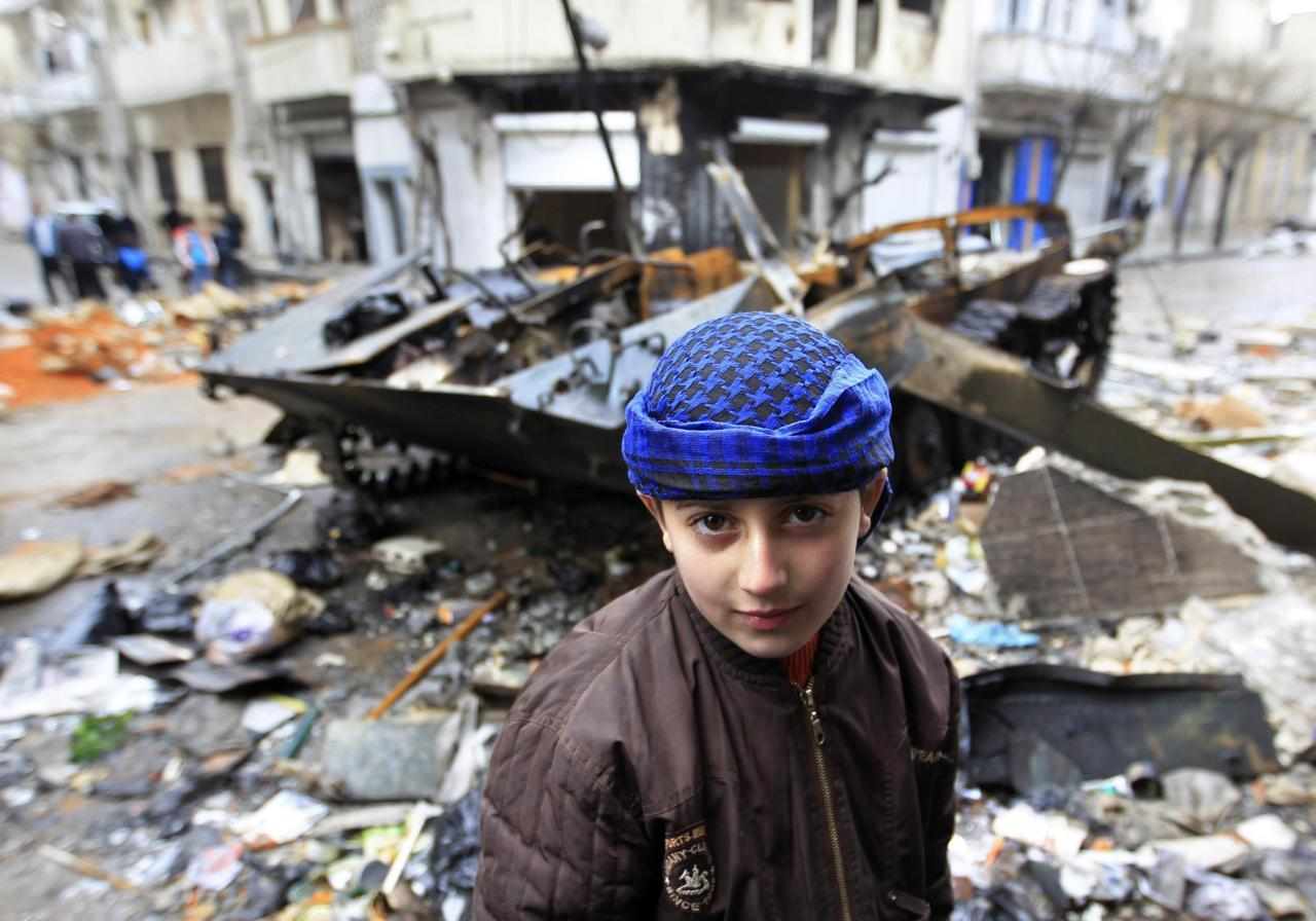 reuters:  A Syrian boy stands in front of a damaged armored vehicle belonging to the Syrian army in a street in Homs January 23, 2012. [REUTERS/Ahmed Jadallah] PHOTOS: More rare images from inside Homs, Syria