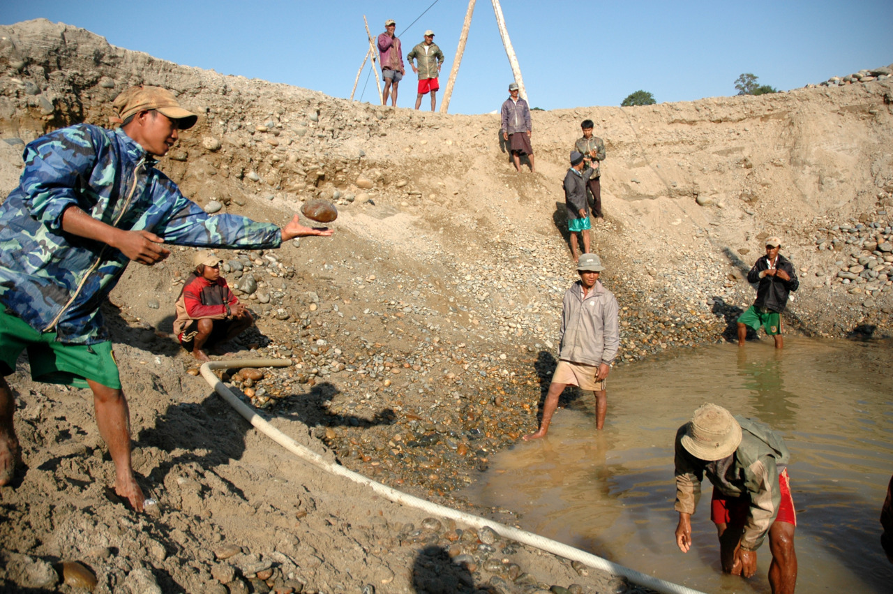 """Monday in the mine: Gold miners form a human chain to toss large rocks out of a new pit mine near the aborted Myitsone Dam project in northern Burma. In order to force local Kachin villagers to relocate from the dam area, the Myanmar government outlawed private gold mining, instead giving the mining concessions in the area to outside companies. These miners are neither locals nor ethnic Kachins, just miners from other parts of the country brought in to work. The dam project, which was financed by China to help feed China's growing need for energy, has been suspended because of local and national outrage over the project. This is, ironically, good news for the miners brought in to replace the locals, because the locals are still not allowed to mine, and now the mines won't be flooded by the dam anytime soon. """"We're glad the dam is suspended,"""" one of them told me. """"We just want to keep working."""" —NT [Photo credit: Nathan Thornburgh / Roads and Kingdoms]"""