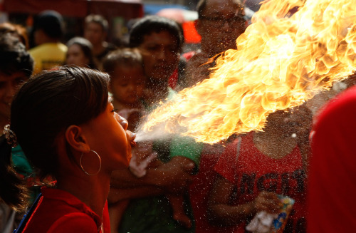 Performer in Philippines breaths fire during dragon dance for Chinese New Year, by Bullit Marquez. via
